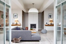 View through open terrace doors to grey corner couch and cat on floor in modern lounge area