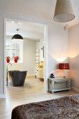 View of grey, free-standing bathtub through open bedroom doorway