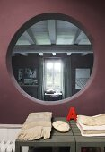 Folded blankets on grey wooden benches below circular aperture in aubergine wall with view of bedroom window