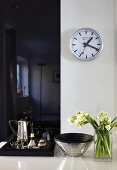 Bouquet in glass vase, elegant bowl and silverware on tray on white surface below wall clock