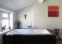 Designer bathtub with angular taps, metal animal sculpture and ceramic pot on windowsill