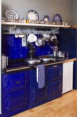 Vintage cooker and splashback in bold blue and cooking utensils hanging from hooks under white, wall-mounted shelf