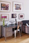 Classic chair and contemporary metal desk below framed pictures on wall