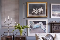 Candelabra and vase of tulips on retro side table in front of framed pictures on pastel wall