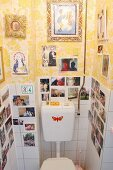 Collection of photos & pictures on tiled and papered walls in toilet