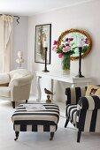 Polstersessel und Fussschemel mit schwarz-weiss gestreiftem Bezug, neben Vintage Konsolentisch, Blumenstrauss vor Spiegel mit antikem Goldrahmen