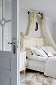 Doppelbett mit transparentem Baldachin, auf Boden weisses Tierfell in ländlichem Schlafzimmer