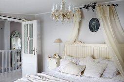 Schlafzimmer mit transparentem Baldachin über Doppelbett, offene Zimmertür mit Glasfüllung