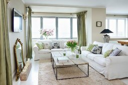 Coffee table with delicate metal frame and rustic wooden top on long-pile rug and white sofa set in corner of living room