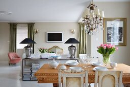 Vase of tulips on solid wooden table in front of sideboard against back of sofa in open-plan interior