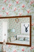 Portrait of stag above double bed reflected in mirror with antique gilt frame on magnolia-patterned floral wallpaper