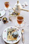 Nostalgisch dekorierter Tisch, Teetassen, Kuchenteller mit alten Backförmchen und Postkarten