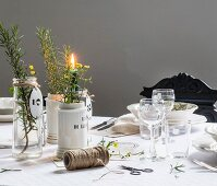 Flowers and herbs in glass and china vases in front of place setting with wine glasses on table