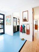 Hallway with wooden flooring and pale blue lino flooring, children's coat rack and open doorway leading into kitchen