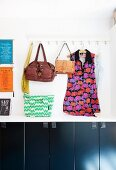 Leather bags and patterned tunic hung from wall hooks above cupboards with black fronts