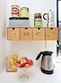 Glasschalen mit Pfirsichen und Zitronen neben Wasserkocher, vor Wand mit Holzboxen in Halterung, obenauf Metalldosen und Kaffeekanne