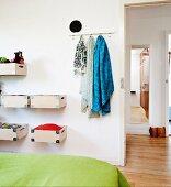 Teilweise sichtbares Bett mit grüner Tagesdecke, gegenüber an Wand montierte Holzboxen und Hakenleiste mit Tüchern, neben offener Tür