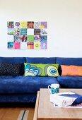Sofa mit blauem Bezug und gemusterte Kissen in Reihe, vor Wand mit modernem Bild