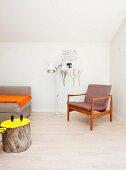 Sessel mit Holzgestell im Fiftiesstil neben Stehleuchte , im Vordergrund Baumstamm als Beistelltisch mit gelb gestrichener Schnittfläche