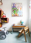 Wooden child's chair with matching table and retro-style, ride-on car on grey-painted wooden floor