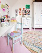 Shabby-chic chair at white desk, rustic half-height cabinet next to wardrobe on wooden floor painted pink