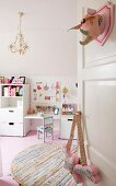 Open door decorated with fabric hunting trophy, round rag rug, pink wooden floor and white furniture in child's bedroom