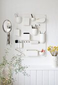 Vanity mirror and make-up in white organiser board above vase of yellow dried flowers on shelf