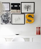 Black and white pictures, drawings and yellow ornamental letter above red candlesticks on white shelf