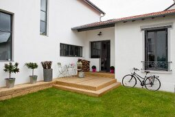 Modern house with rustic wooden terrace, lawn and bicycle