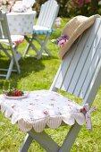 Romantisches geblümtes Sitzkissen auf hellgrauem Gartenstuhl mit Erdbeerteller und Sonnenhut dekoriert