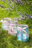 Drei Glaswindlichter mit romantischem Blumenmuster dekoriert und nostalgischem Flair im Gras neben Lavendelblüten im Garten