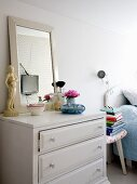 Make-up brushes and framed mirror on chest of drawers next to three-legged stool and bed in bedroom