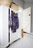Floral dress hung from wardrobe on clothes hanger in bedroom with patterned wallpaper