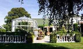 Steinbalustrade um sonnenbeschienene Terrasse mit Wintergarten