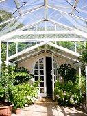 Wintergarten aus Stahl und Glas an Landhaus mit Rundbogentür, blühende Rosen in Töpfen