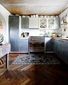 Fitted kitchen with grey mottled doors in simple kitchen with vintage rug on herringbone floor