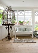 Vintage bird cage on ornate metal stand and white bench in wood-clad conservatory