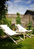 Bamboo sun loungers with pale cushions on lawn in front of willow screen