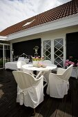 Chairs with white loose covers at round table on wooden terrace outside house with black and white façade