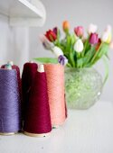 Colourful reels of thread with vase of tulips in blurred background
