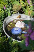Pink flower and blue-painted pebbles in miniature pond in zinc tub