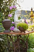 Planters and stone statue on vintage sewing machine base in garden