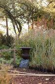 Amphore und Schrifttafel vor Graspflanzen in Gärtnerei