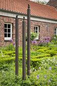 Kunstobjekt aus drei Stelen mit Vogelfigur im Vorgarten, im Hintergrund Bauernhaus aus Ziegel