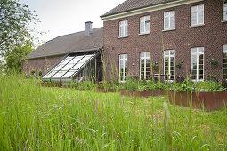Blick von wildem Garten auf Hochbeete mit Metalleinfassung vor renoviertem Bauernhaus aus Ziegel