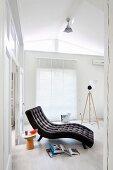 Anthrazitfarbene Liege mit Polsterknöpfen in puristischem, weissem Raum, Beistellhocker und Bücher am Boden