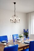 Crystal chandelier above set table with chairs upholstered in royal blue and vase of delphiniums in background