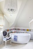 Surface covered in mosaic of colourful tile shards and tiled border behind free-standing bathtub and antique chair; chandelier with lampshade in foreground