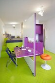 Modular kitchen with integrated dining table and bed on platform with storage space in colourful mini-apartment