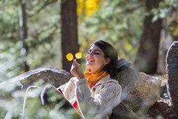 Frau in Wanderkleidung sitzt an Felsen gelehnt auf herbstlicher Waldlichtung